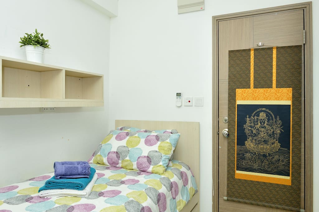 Room door, bed, and shelve above the bed