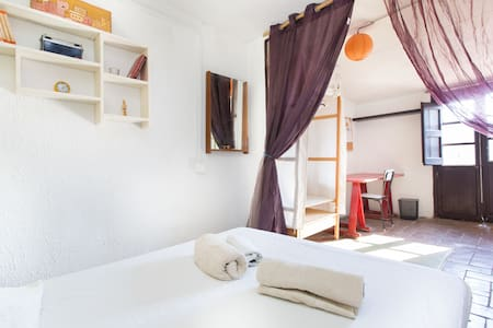 In El Born, the coolest area in the heart of the city. A big, sunny, quite, cozy, artistic room, as the flat, with balcony to the best square of the area. Just behind the Picasso Museum. Very close to the park, 10 minutes walking to the Barceloneta.