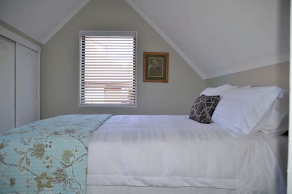 Upstairs bedroom with Queen sized luxurious bed and top quality linen