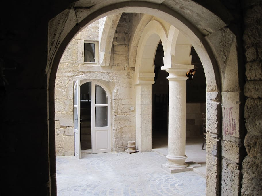 Courtyard looking from the vaulted main entrance, door leading to stairs and summer room to the right