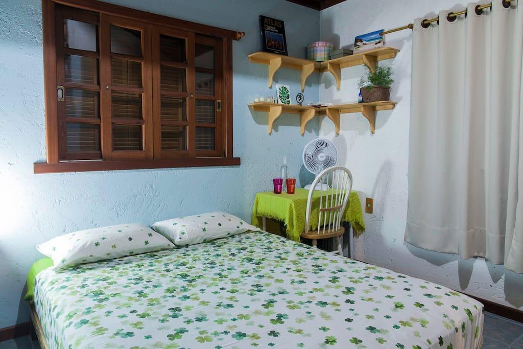 Quarto com cama queen, mesa de apoio com cadeira, ventilador, espelho e amplo guarda-roupas.
