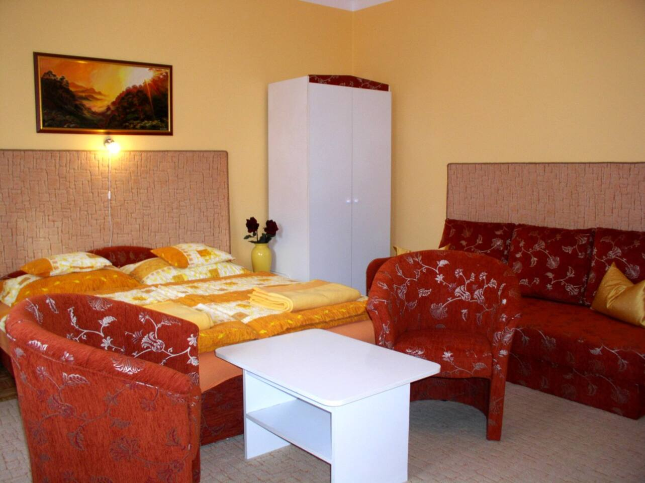 Private room with a mini kitchen, a double bed and a singel bed.