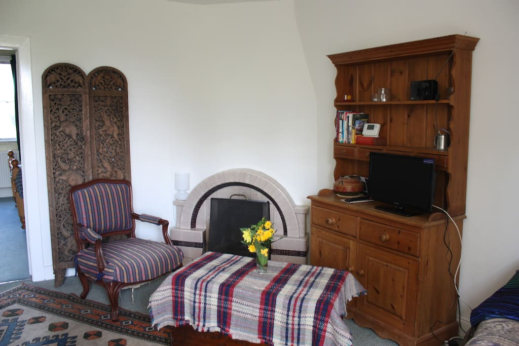 Sitting room, with TV to watch DVDs on. Behind the chair is the wooden screen that can be used to shield the sofa bed.