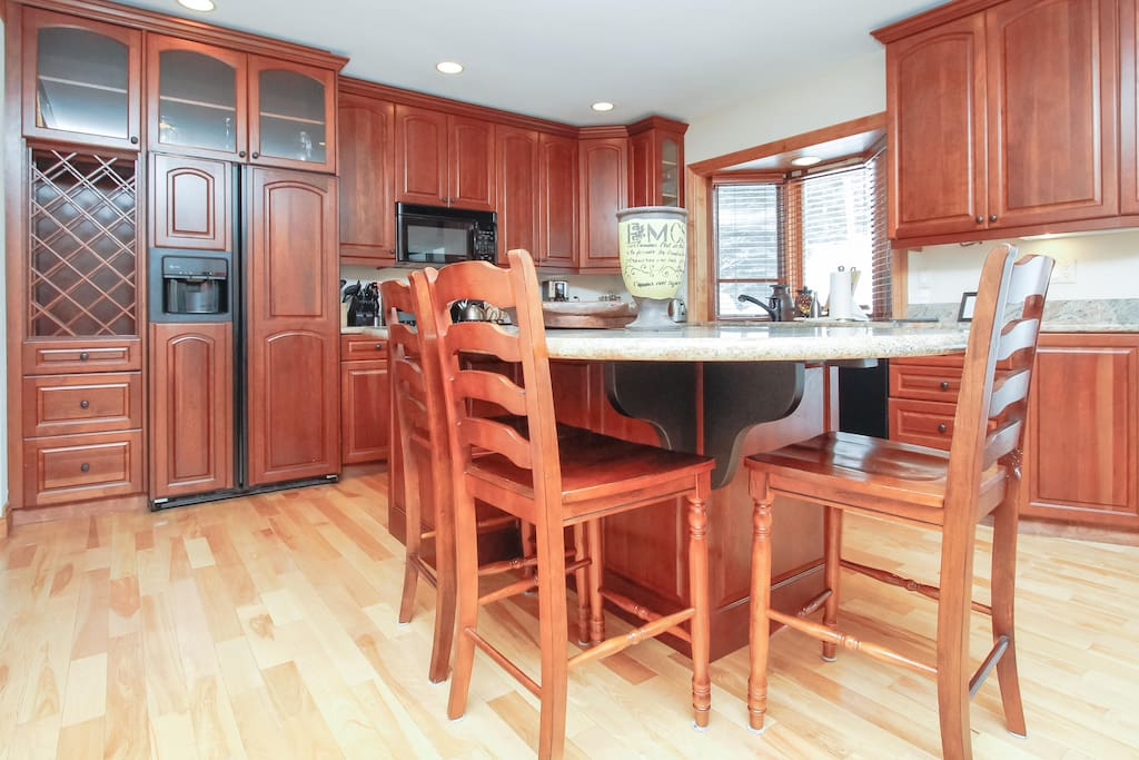 Kitchen features everything you'll need, and includes granite counters and large island with four stools.