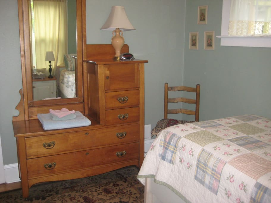 Dresser and chair in twin room. Guest towels on dresser. alarm clock.