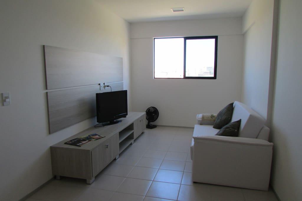 Sala com TV, ventilador e sofá-cama
