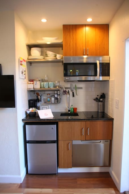 New kitchen with granite counter,  cooktop, refrigerator, microwave, dishwasher.