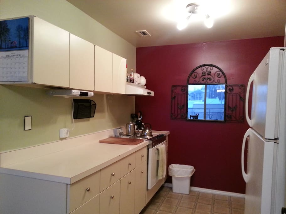 Galley kitchen with refrigerator and microwave...