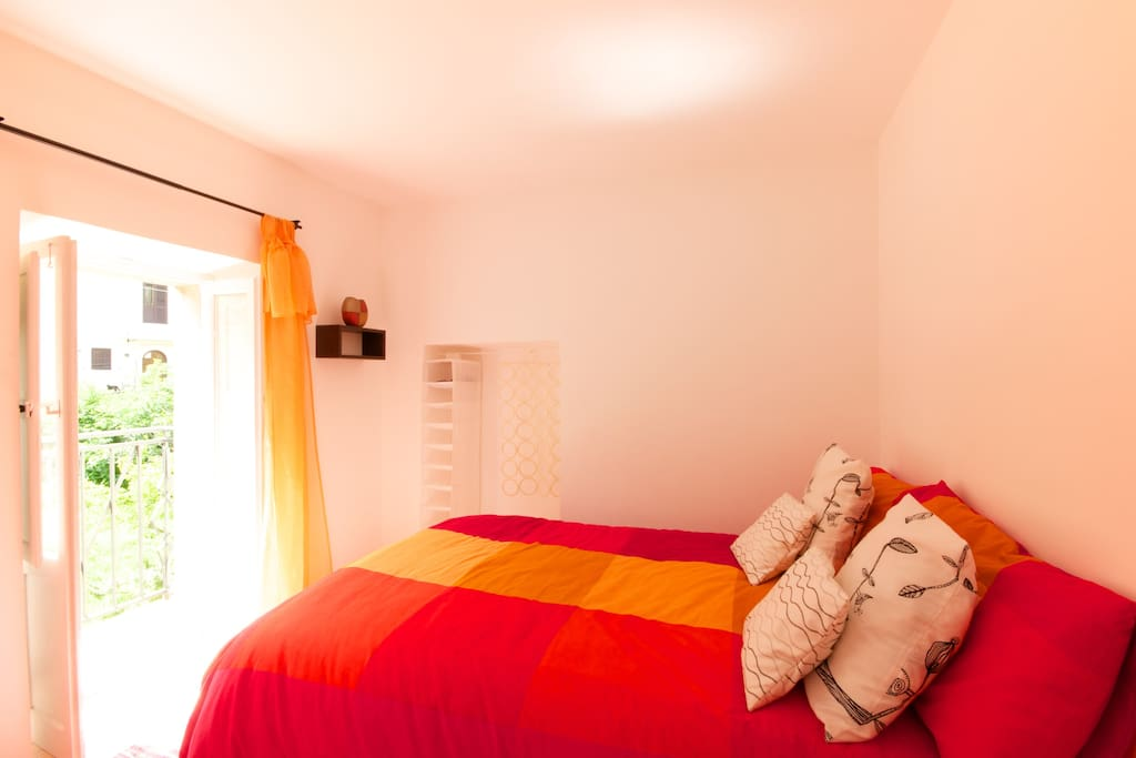 Smaller second bedroom with a private balcony overlooking the town