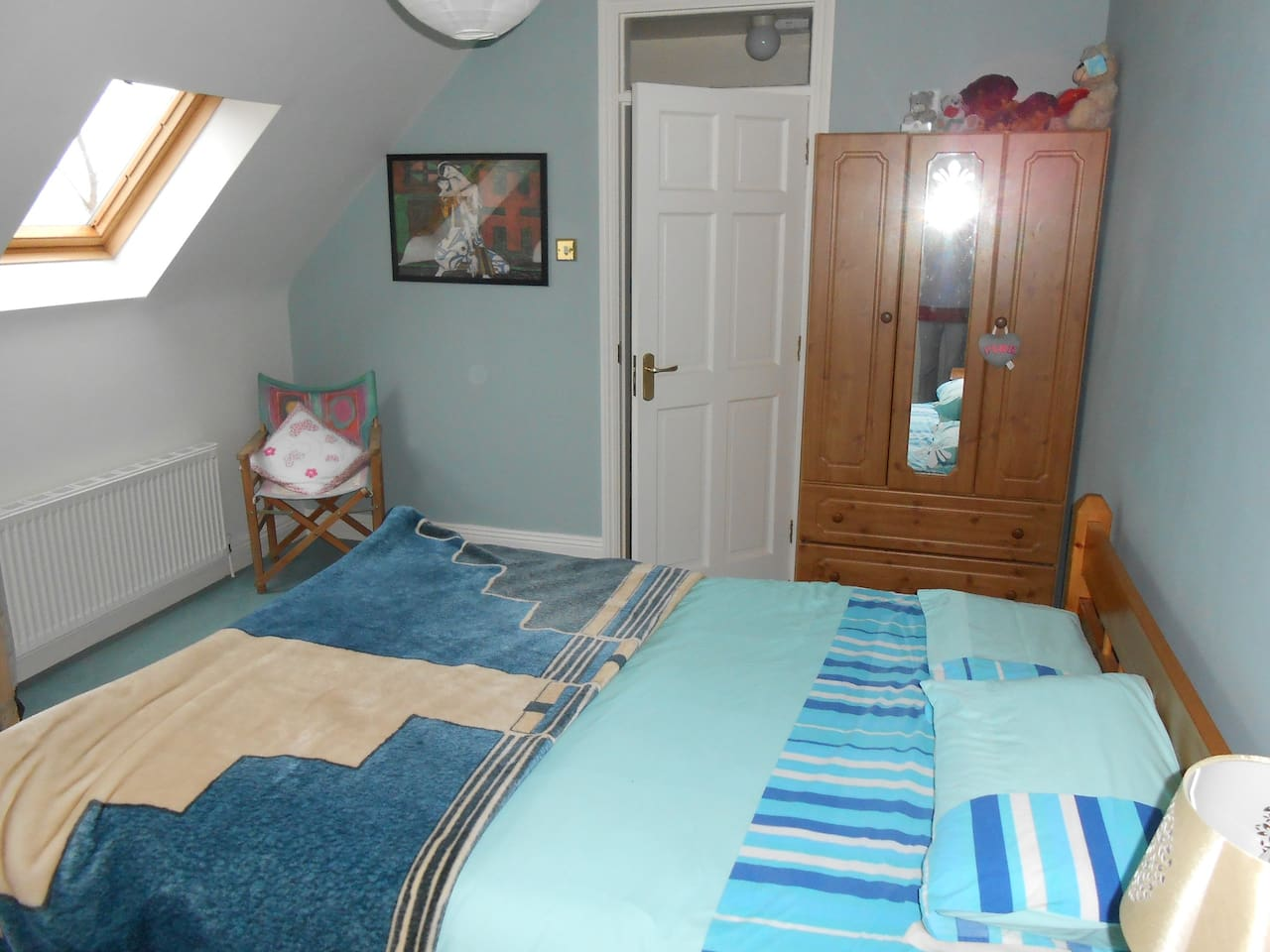 Blue double bedroom with  shower room and king-size bed.