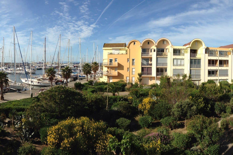 Vue panoramique de la terrasse sur le jardin arboré et la marina