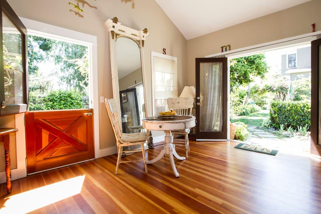 Eating nook floats between the wooden french doors and Double Dutch door that open to the serene gardens.