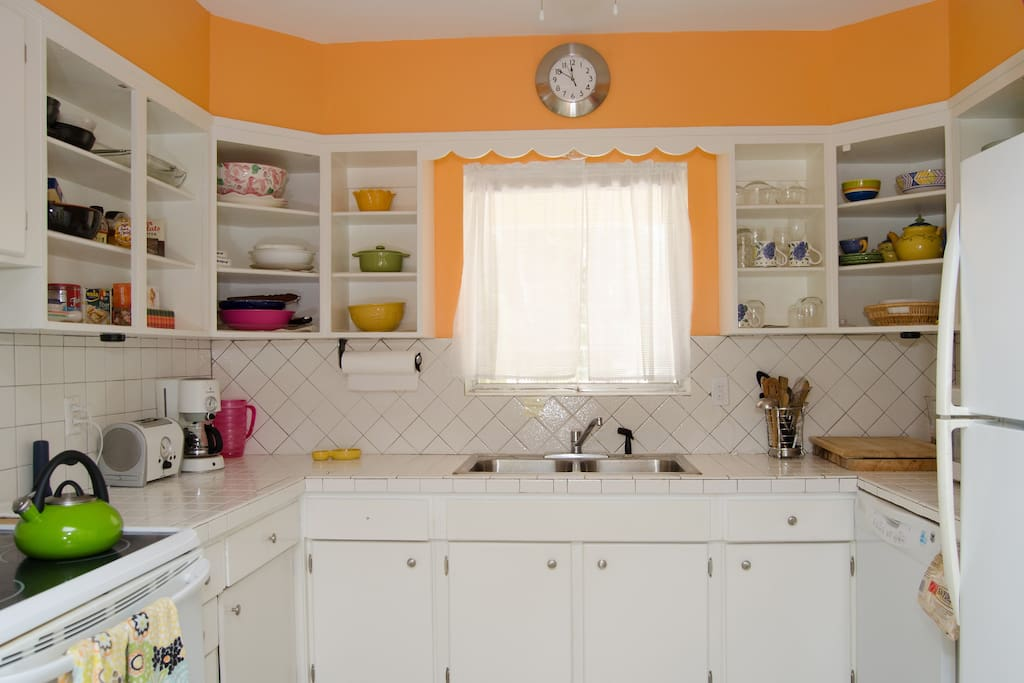 Brightly colored kitchen to highlight original white wood cabinets and tiled countertop/ backsplash.