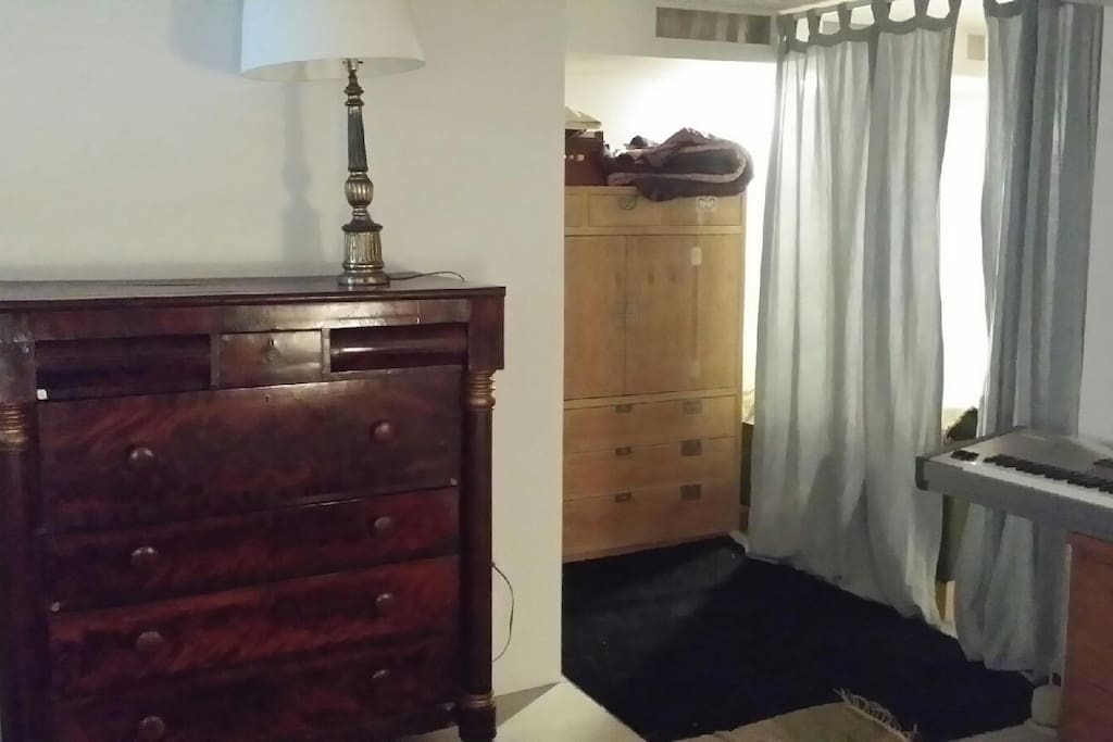 Curtains separate from living studio with fridge and hotplate.