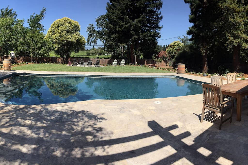 Large travertine pool deck with dining area overlooking beautiful vineyard view and amazing sunsets.