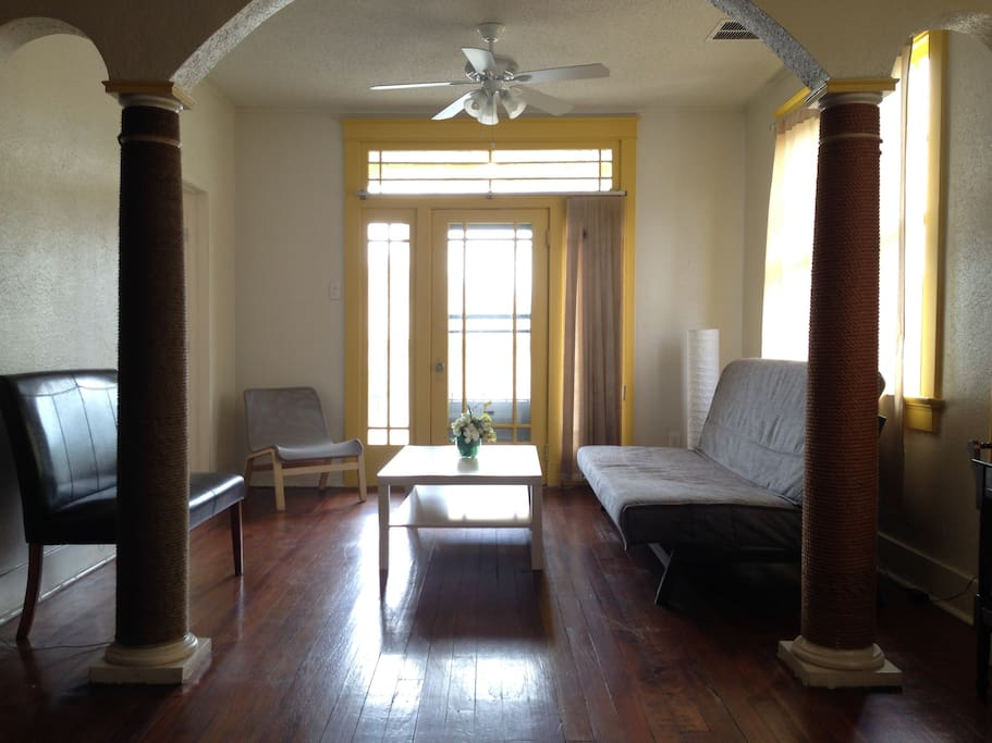 Living room with door to balcony over the front corner of house. The sofa on the right pulls out into a fill-sized bed and has a compartment storing sheets underneath.