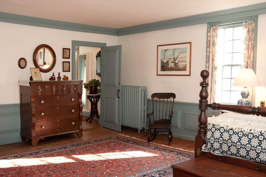 The room has a tiled fireplace and a table.
