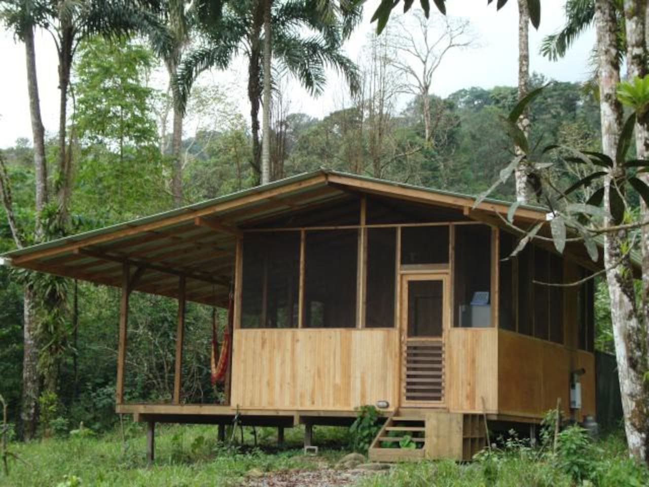 Howler Monkey Hideaway is a wood cabina with large open roofed deck on the side.