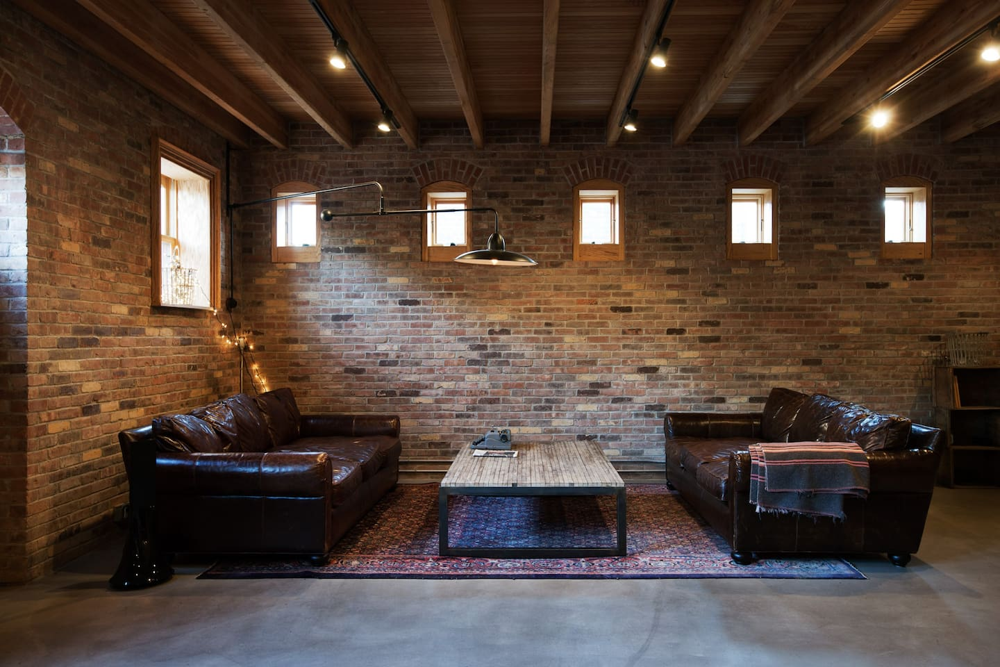 Twin leather couches and recycled bowling alley wood table. Windows for horses' heads