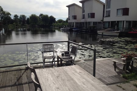 5-star house for people that loves to be around water. Located in the middle of the three major cities and 12 minutes from Schiphol airport. Next to the house is a boat and canoe rental and the necessary shops are just around the corner.