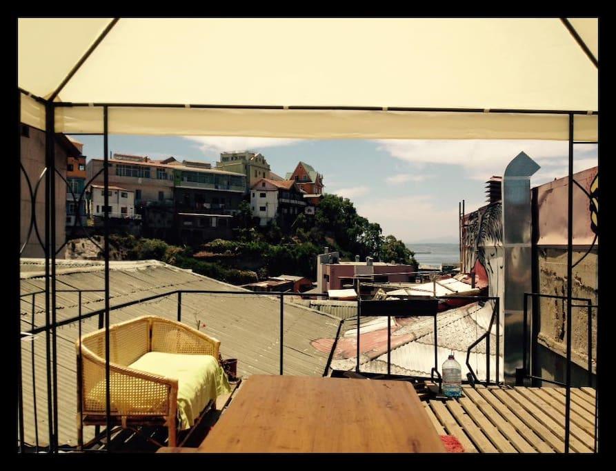 Hermosa terraza sobre el techo en donde tendrás una increíble vista  al mar y los cerros mientras disfrutas tus desayunos, almuerzos o cenas, como también gratas conversaciones con los demás turistas.