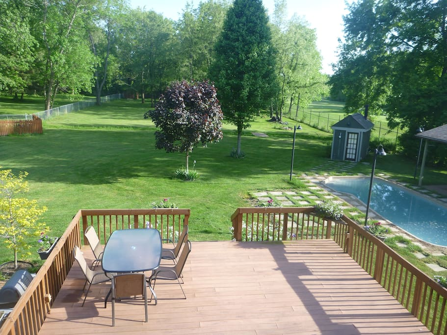 View of our back yard from Guest Room, showing our  deck & pool. A small creek bisects our yard. And Mud Run Golf course is off to the right.