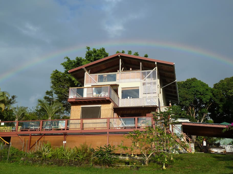 An ocean side view of the main house, near where you will share the community kitchen, blessed by a rainbow overhead.