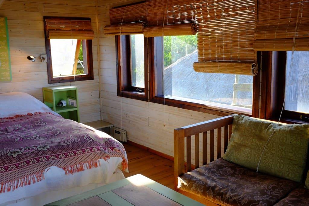 The bedroom has a double bed, mosquito net and repellent, safety box, bedside lamps, a wardrobe, table, chairs, ventilator fan and a balcony