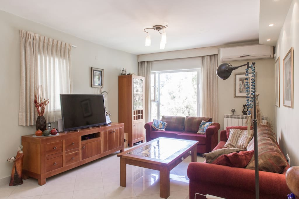 living room with flat screen TV,large picture window overlooking the botanic gardens