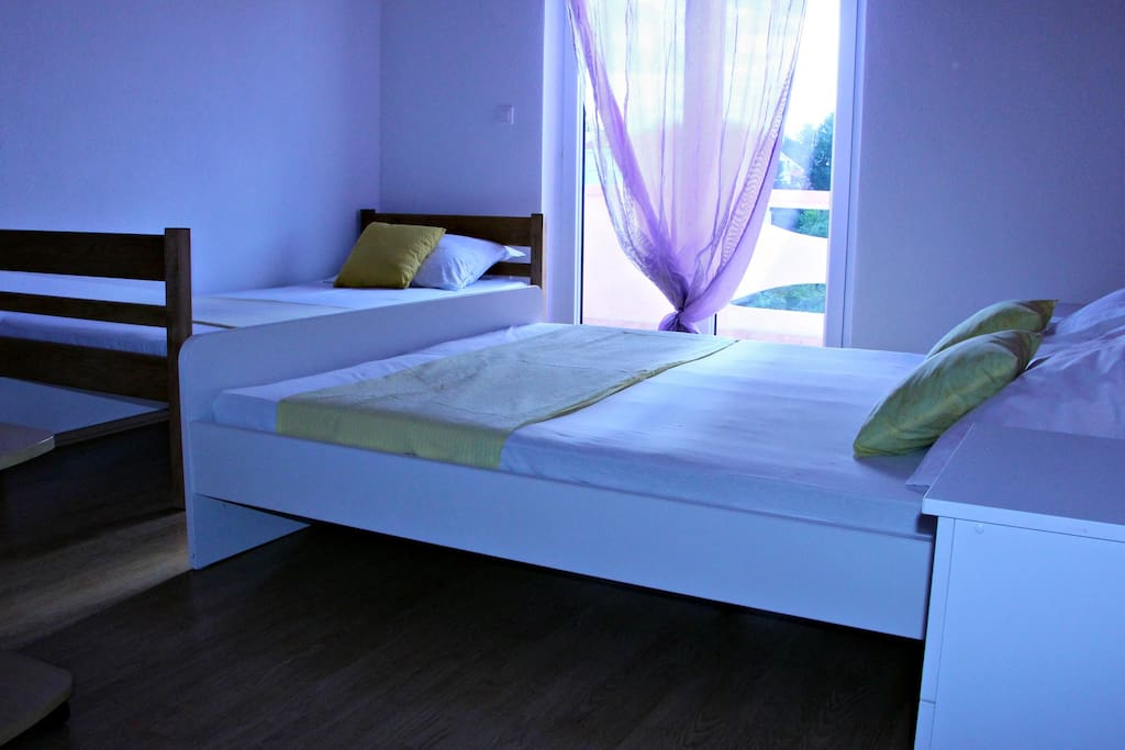 Bedroom with big comfortable double bed and single bed