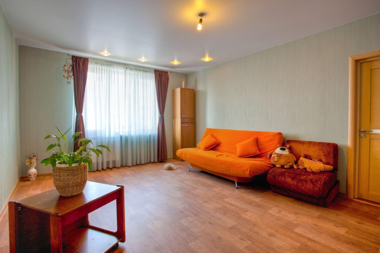 Spacious room with orange sofa-bed
