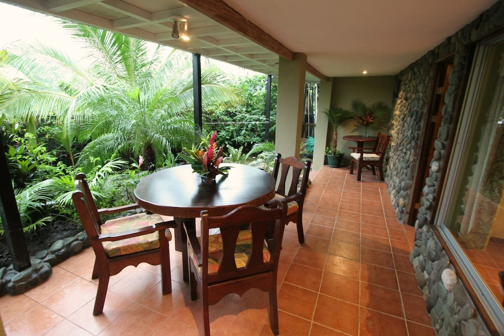 The porch overlooks the lush gardens and waterfall