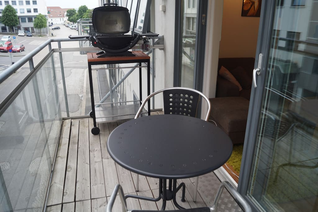 Balcony with dining table and gas BBQ.
