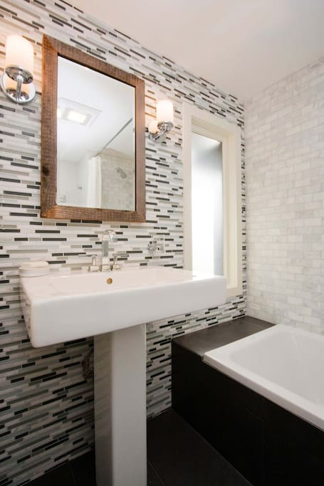efficient bath with tub/shower and sleek, modern fixtures, even a towel warmer!