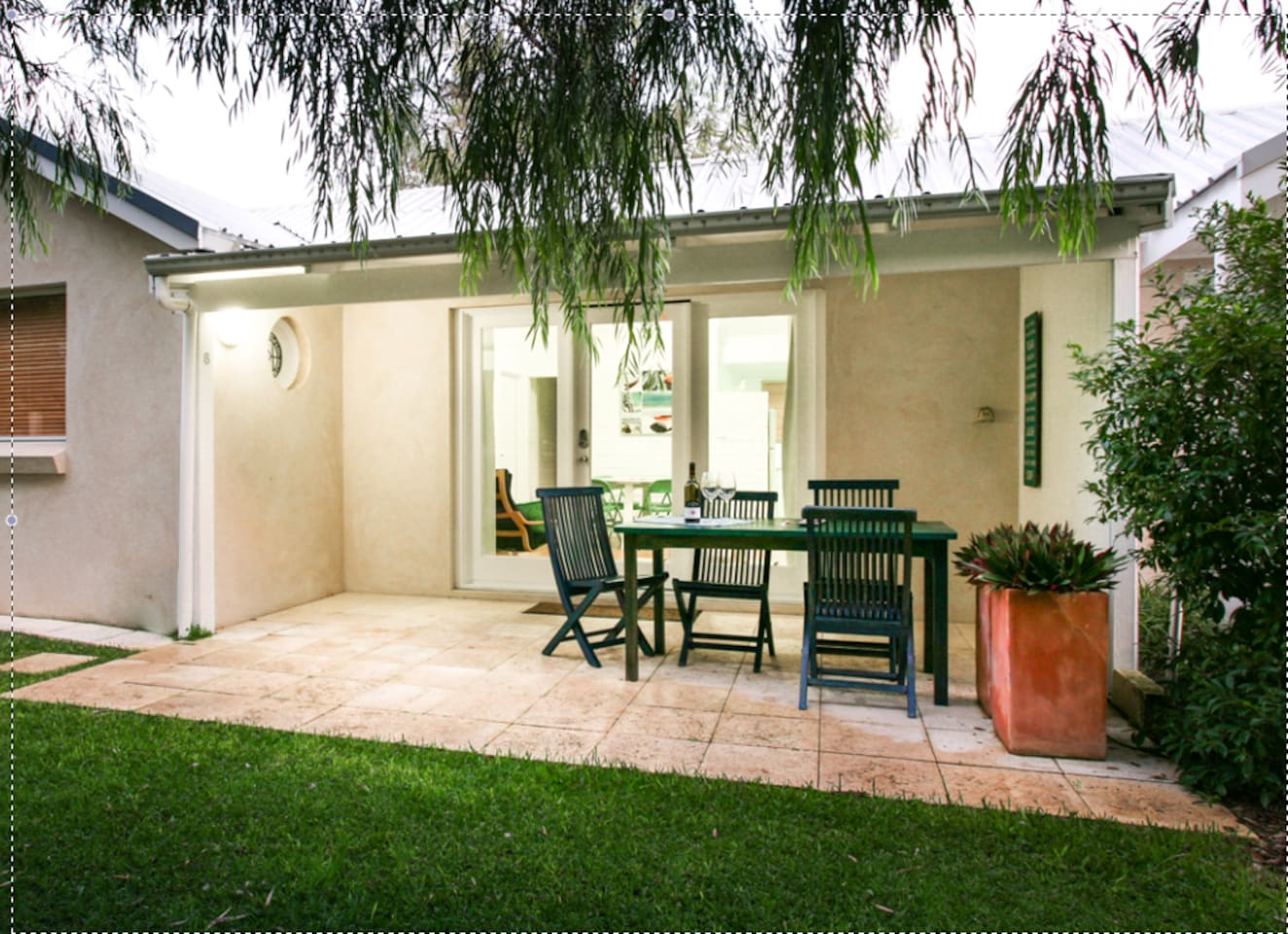 Outdoor setting of the villa, with large lawned area & parking bay