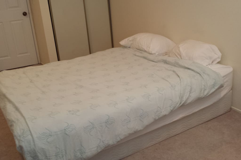 Queen bed with two pillows, sheets and comforter