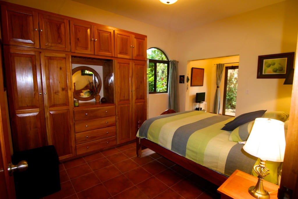Garden Suite with queen size bed, sitting area, french doors open to garden