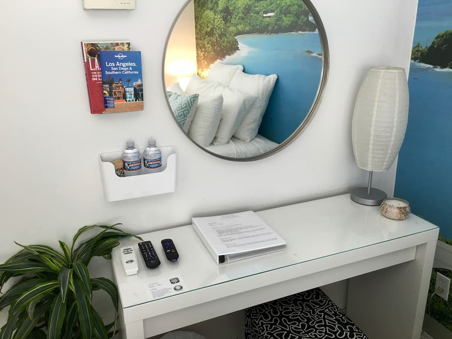 Dressing table with bottled water, Clif bars, LA guidebooks