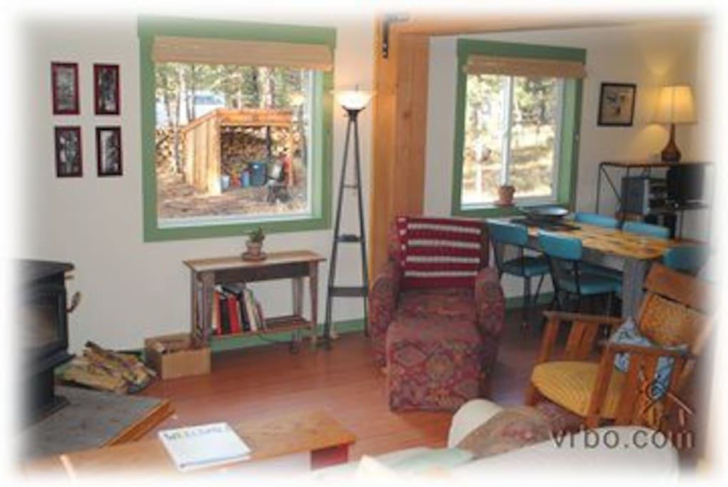 Living room with wood stove, dining table and lots of comfortable chairs and a couch!