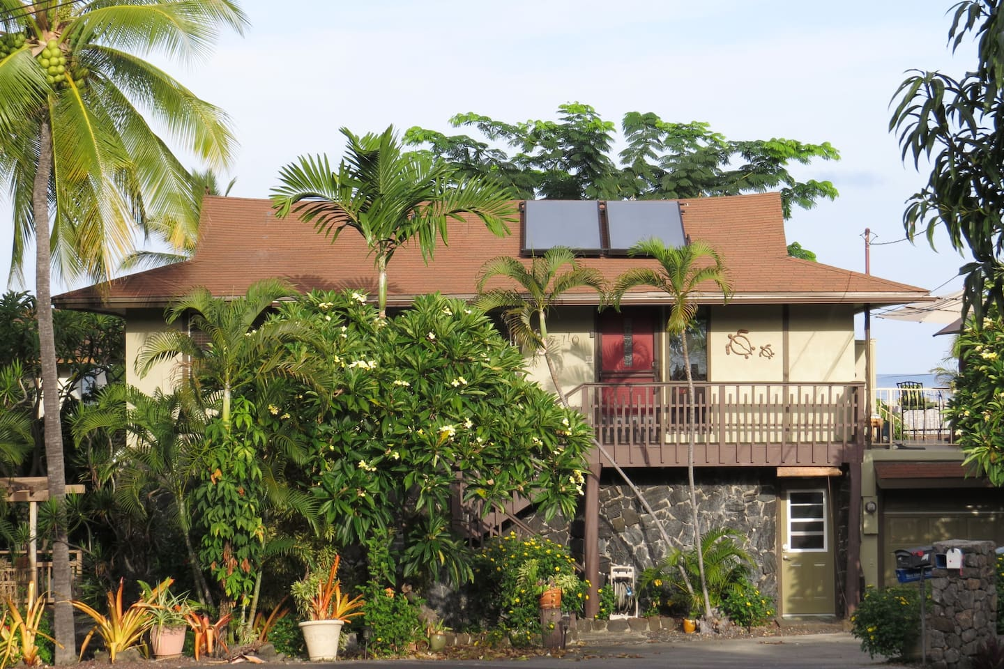 Street side view of house with ocean in the background.  Apartment door is in lower right corner.