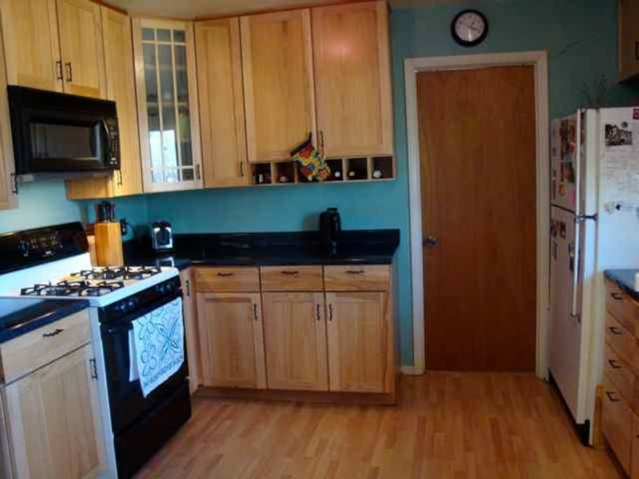 Gas range, microwave, Pergo floor & hickory cabinets create a nice workspace.