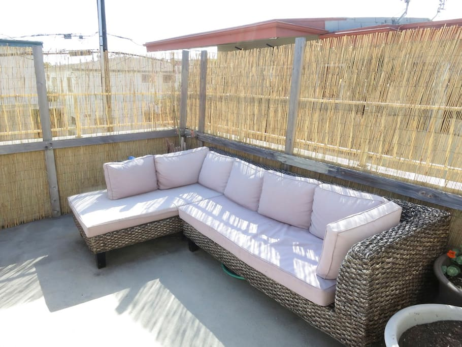 The outdoor patio is large, private and features a large outdoor sofa.