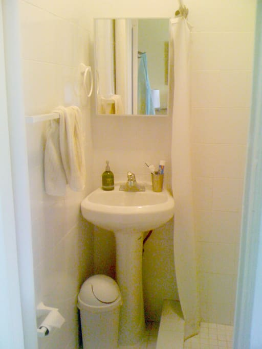 Clean, white-tiled bathroom with shower.