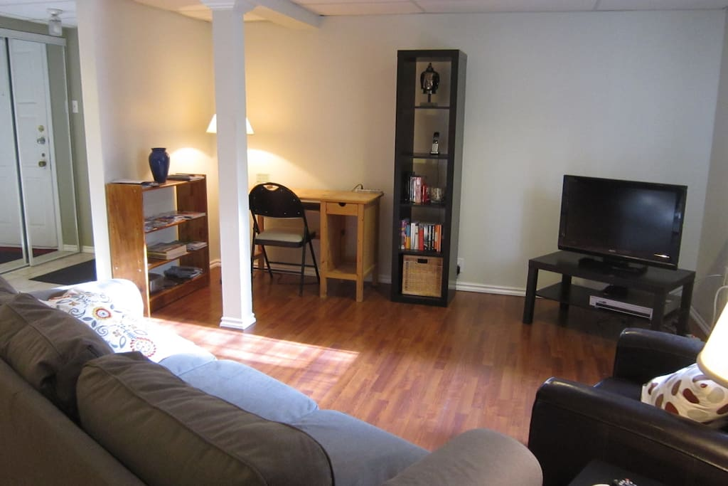 Living Room with cable TV, wifi, DVD player, desk, sofa and armchair.