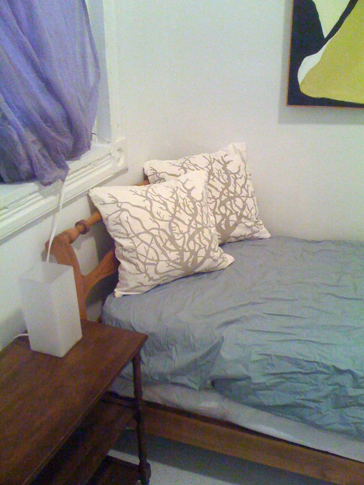 Available room with antique bed and adorned with artwork...