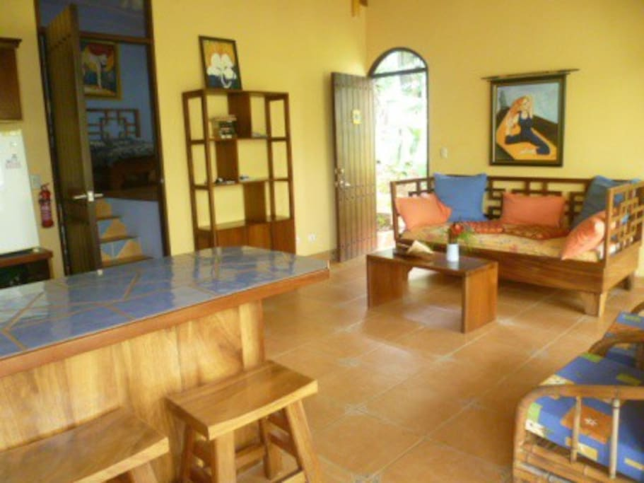 the villa living area with full kitchen to the left and sitting area or extra bed