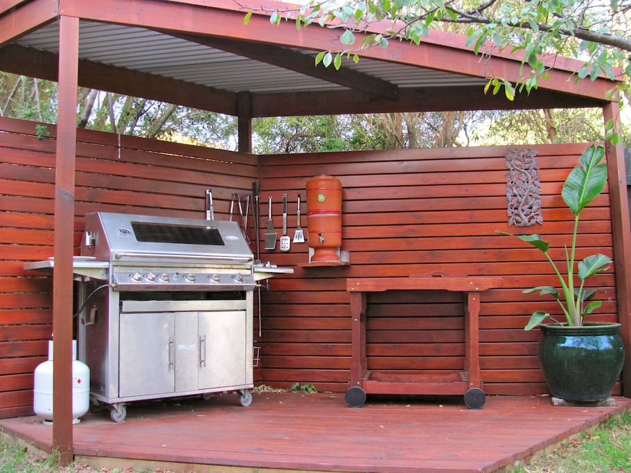 A covered BBQ area adjoins the decking, lawn, and garden; with a large grill and wok burner.