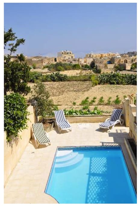 Lounge by the pool with the view of Ta' Pinu and the Gharb valley.