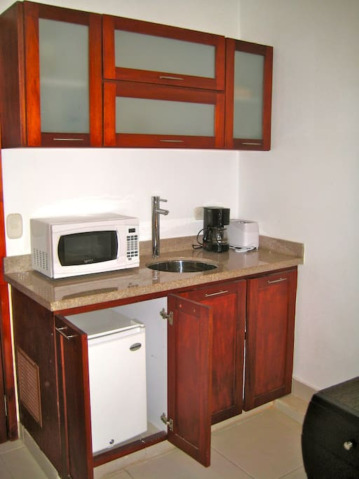 The mini-kitchen has a small refrigerator, microwave, toaster, coffee pot, electric skillet, dishes & utensils