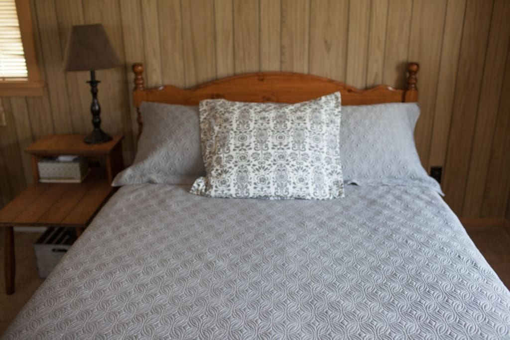Comfortable and clean, QUEEN-sized bed for two with mattress topper, end tables and lamps.